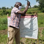 The Water Project: Musango Community, Ndalusia Spring -  Facilitator Installing Reminder Chart At The Spring