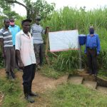 The Water Project: Lukova Community, Wasike Spring -  Community Members At The Spring Installing Reminder Chart