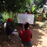 The Water Project: Emulakha Community, Nalianya Spring -  Facilitator Holding Up The Teaching Aid