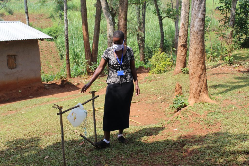 The Water Project : covid19-kenya19118-the-facilitator-demonstrating-how-to-use-the-handwashing-station