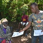 The Water Project: Shamiloli Community, Kwasasala Spring -  Issuing Handouts To Participants