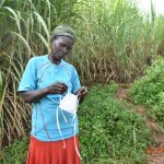 The Water Project: Ataku Community, Ngache Spring -  Catherine Puts On Her Mask