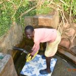 The Water Project: Ataku Community, Ngache Spring -  Catherines Granddaughter Fetching Water From Ngache Spring