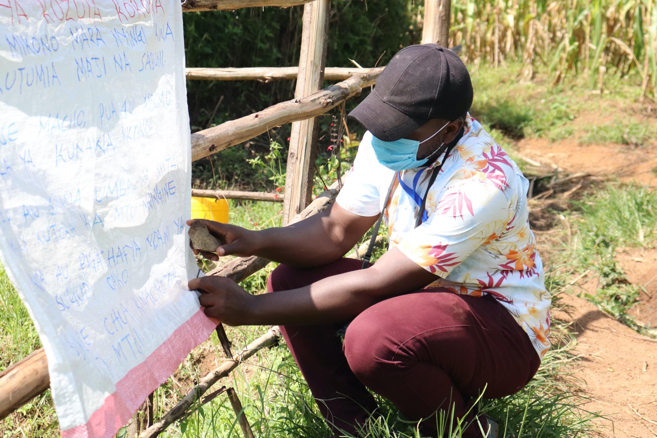 The Water Project : covid19-kenya20162-sir-allan-mounting-the-chart-on-the-poles-at-jairus-mwera-spring-1
