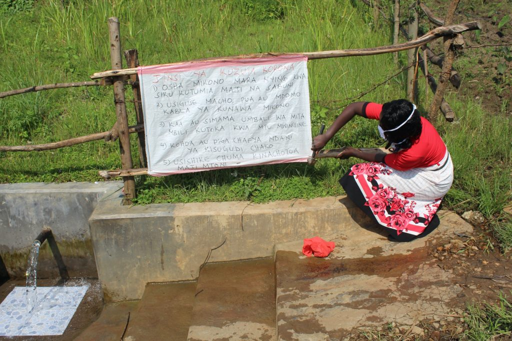 The Water Project : covid19-kenya20168-installing-covid-poster-at-the-spring-3