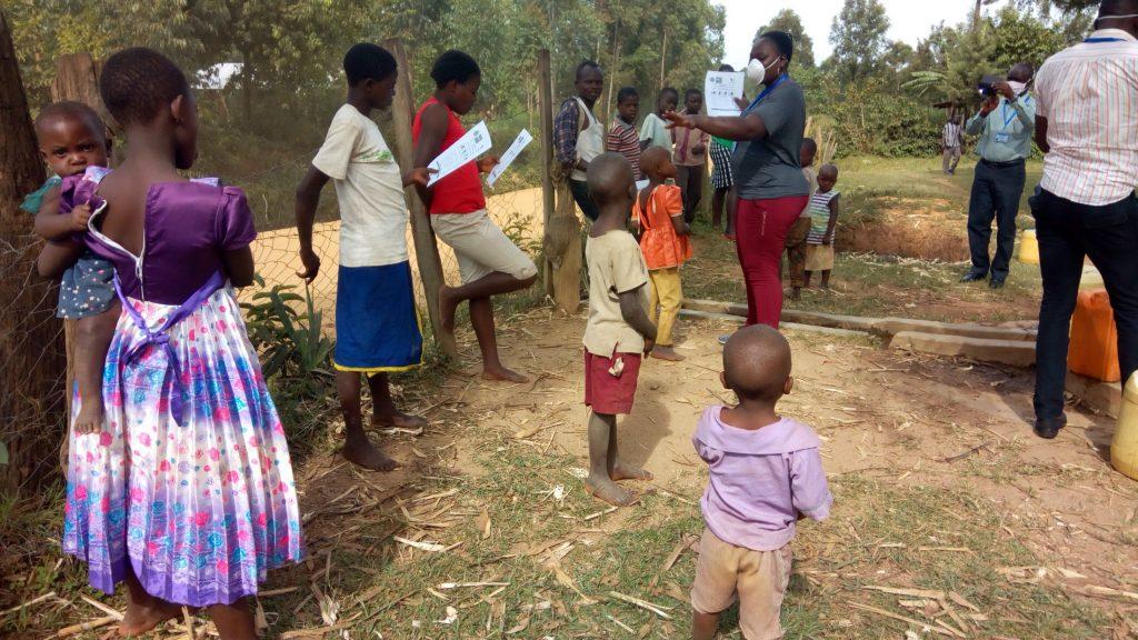 The Water Project : covid19-kenya4332-community-members-read-covid-flyer