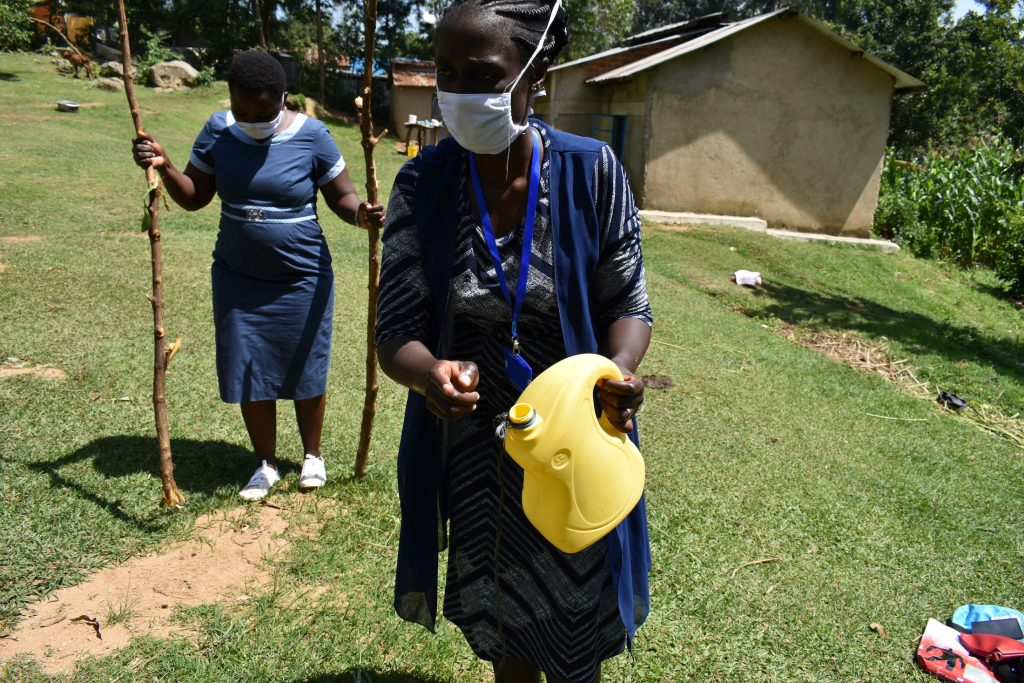 The Water Project : covid19-kenya4418-the-faciliators-demonstrating-how-to-make-simple-handwashing-stations