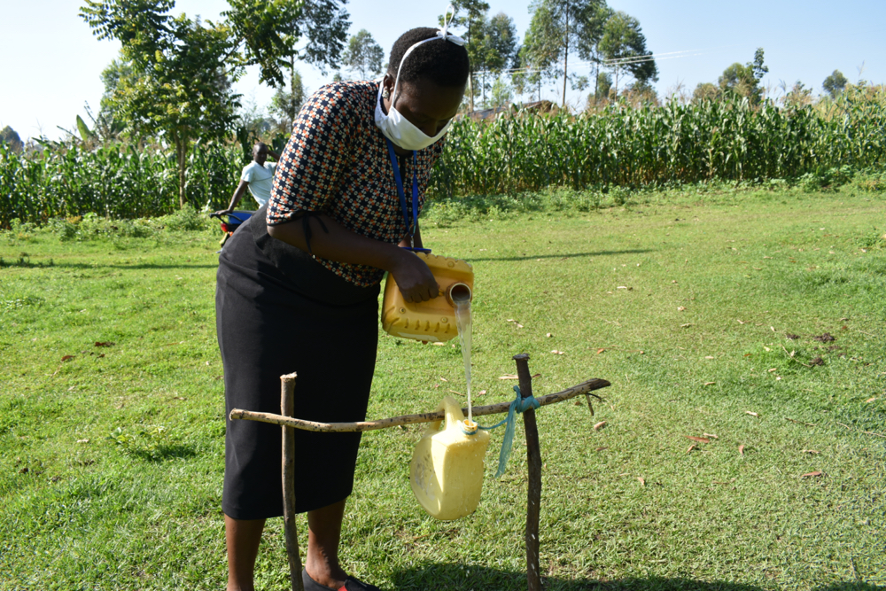 The Water Project : covid19-kenya4576-ms-karen-filling-the-container-with-water