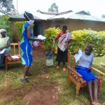 The Water Project: Munzakula Community, Musonye Spring -  Mrs Wagaka Issuing Out The Training Documents