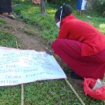The Water Project: Handidi Community, Malezi Spring -  Mounting The Chart To Support Poles