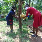 The Water Project: Ebung'ayo Community, Wycliffe Spring -  Mrs Wagaka Helps Team Leader Catherine Use The Leaky Tin