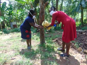 The Water Project:  Mrs Wagaka Helps Team Leader Catherine Use The Leaky Tin