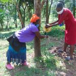 The Water Project: Ebung'ayo Community, Wycliffe Spring -  The Facilitator Helping A Community Member Clean Her Hands