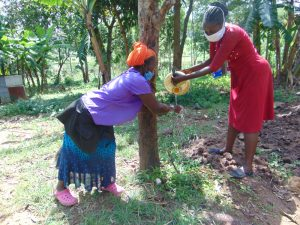The Water Project:  The Facilitator Helping A Community Member Clean Her Hands