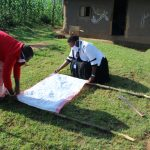 The Water Project: Shiamboko Community, Oluchinji Spring -  Mounting The Chart To Support Poles