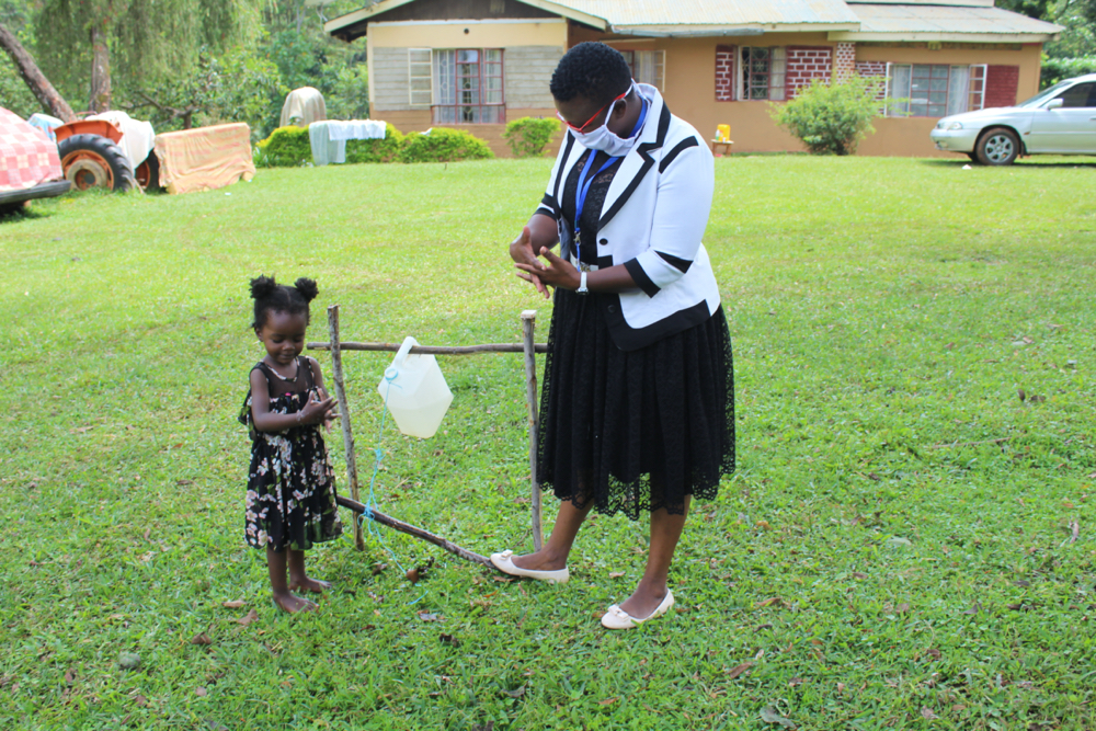 The Water Project : covid19-kenya4738-little-girl-was-not-going-to-be-left-behind-in-handwashing