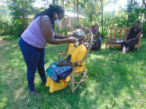 The Water Project:  Trying Mask On An Elderly Lady