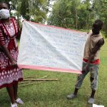 The Water Project: Ematiha Community, Ayubu Spring -  Reviewing The Prevention Reminders Chart