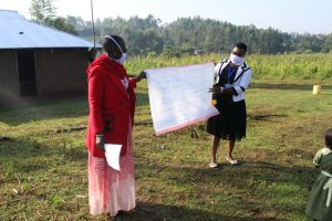 The Water Project:  The Facilitators Holding Up The Teaching Aid