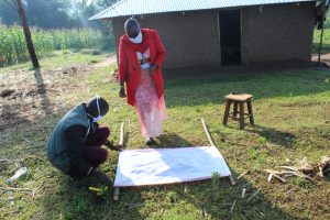 The Water Project:  Trainers Mounting The Chart To Support Poles