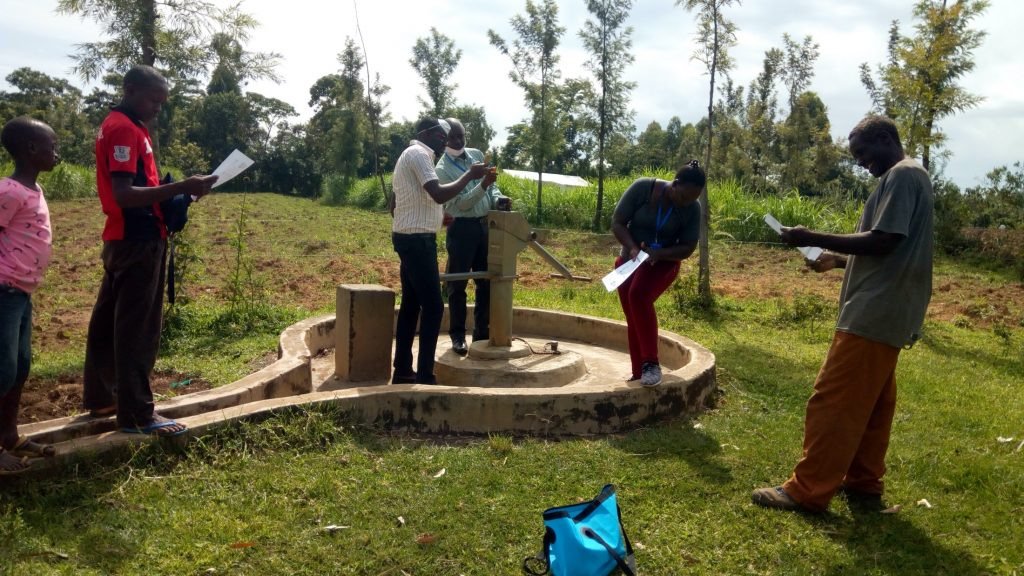 The Water Project : covid19-kenya494-community-members-read-through-covid-prevention-flyer