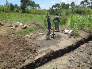 The Water Project:  Women Deliver Materials Next To Spring Drainage Channel