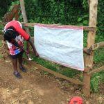 The Water Project: Harambee Community, Elijah Kwalanda Spring -  Installing Covid Poster At The Spring
