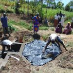 The Water Project: Mukhuyu Community, Chisombe Spring -  Plastic Tarp Backfilling