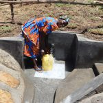 The Water Project: Mukhuyu Community, Chisombe Spring -  Community Member Collecting Water