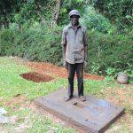 The Water Project: Harambee Community, Elijah Kwalanda Spring -  Chair Keri Tsimonjere Smiles With His New Sanplat