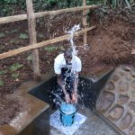 The Water Project: Harambee Community, Elijah Kwalanda Spring -  Lead Field Officer Wilson Celebrates Clean Water