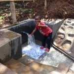 The Water Project: Harambee Community, Elijah Kwalanda Spring -  A Young Girl Touching Water
