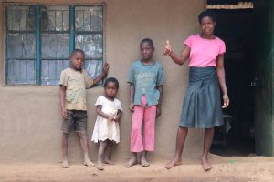 The Water Project:  Magdalene With Her Family Outside Her House