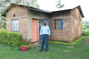 The Water Project:  Henry In Front Of His House