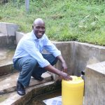 The Water Project: Emachembe Community, Hosea Spring -  Henry Smiles While Fetching Water