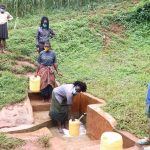The Water Project: Hirumbi Community, Khalembi Spring -  Alice Fetching Water