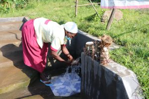 The Water Project:  Mrs Kusimba Uses Spring Water To Rinse Tubers