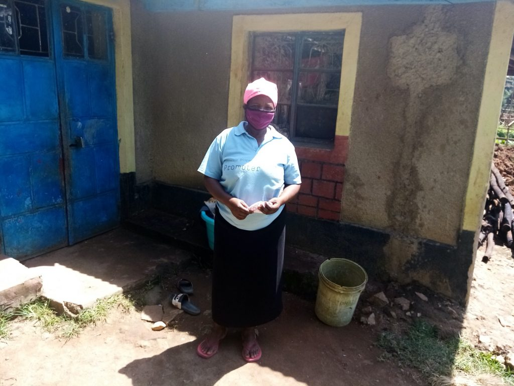The Water Project : covid19-kenya499-otipa-rebecca-wearing-a-facemask-outside-her-home