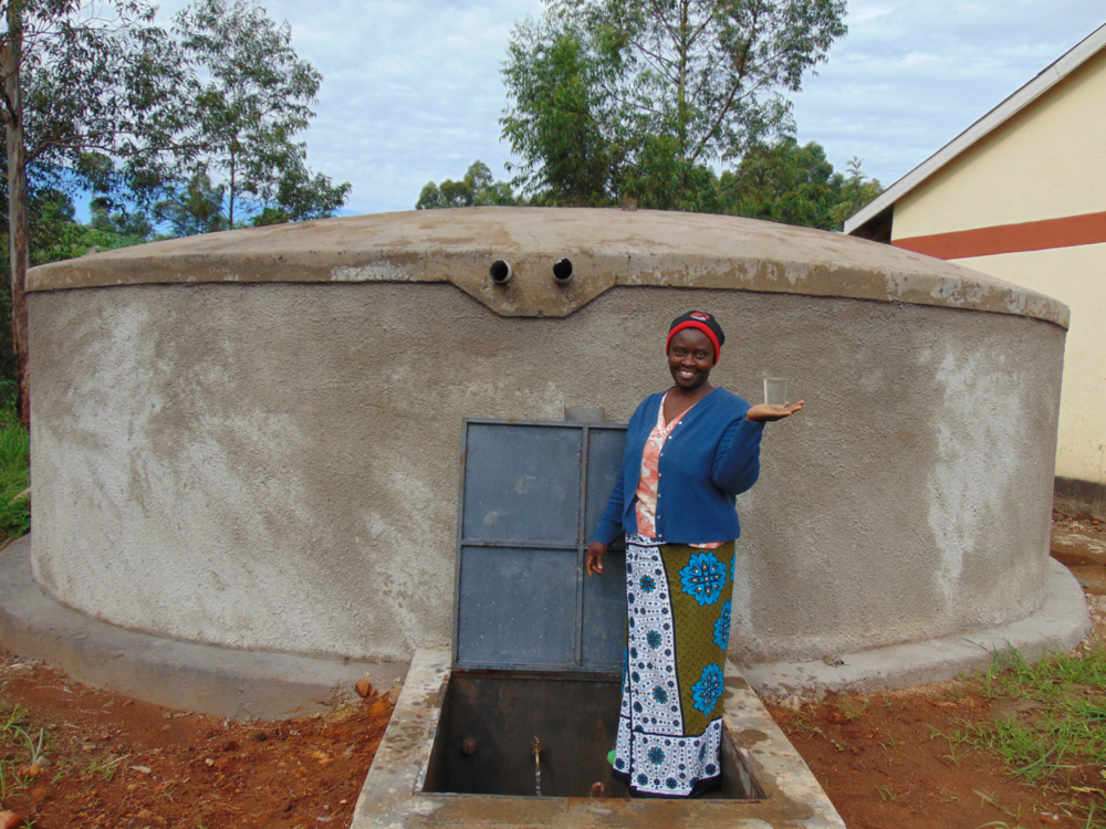 The Water Project : kenya20117-school-staff-holds-cup-of-clean-water-from-tank