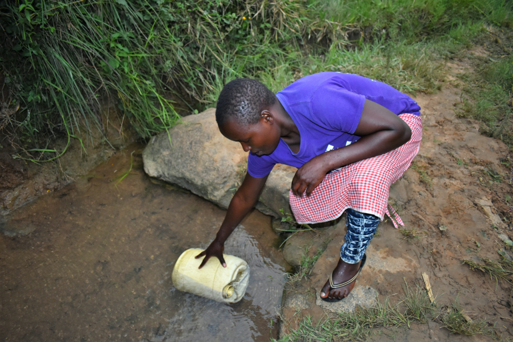 The Water Project : kenya20224-nelly-submerges-her-container-to-fetch-water-1