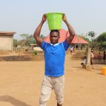 The Water Project: Lungi, New London, Saint Dominic's Catholic Church -  Young Man Carrying Water
