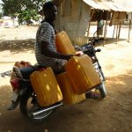 The Water Project: Lungi, New London, Saint Dominic's Catholic Church -  Young Man With Containers To Collect Water