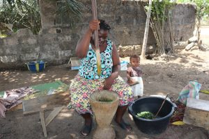 The Water Project:  Woman Pounding Cassava Leaves