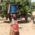 The Water Project: Lungi, Suctarr, #1 Kabbia Lane -  Woman Carrying Water