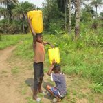 The Water Project: Lokomasama, Conteya Village -  Helping Mount Container On His Head