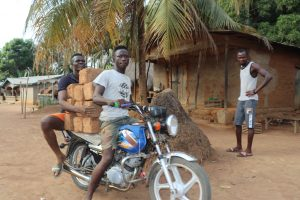 The Water Project:  Young Men Transporting Mud Blocks On Motorbike