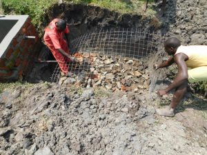 The Water Project:  Laying Wiremesh Over Rock Foundation