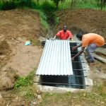 The Water Project: Ikonyero Community, Jesse Spring -  Fitting Metal Sheet To Top Slab
