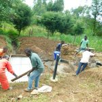 The Water Project: Ikonyero Community, Jesse Spring -  Building Barriers For Slab Cement