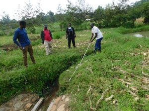 The Water Project:  Humphrey Shows Measurement Of Proposed New Drainage